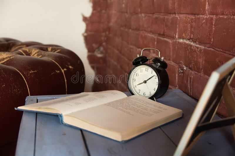 Schreibtischuhr mit einem offenen Buch auf einem Holztisch gegen einen Backsteinmauerhintergrund lizenzfreie stockfotografie