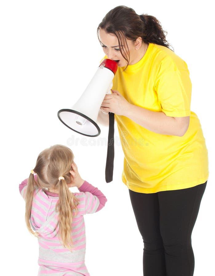 Schreiende fette Mutter, Megaphon und kleines Mädchen stockfotos