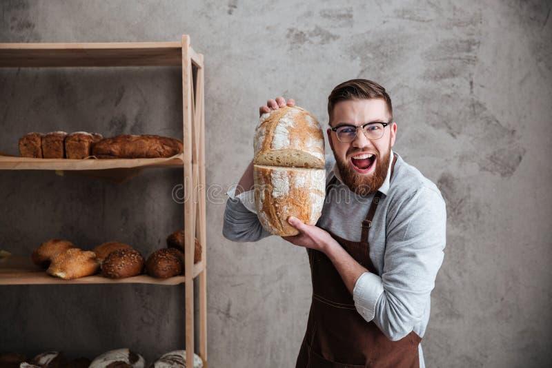 Schreiender Bäcker des jungen Mannes, der an der Bäckerei hält Brot steht lizenzfreie stockfotos