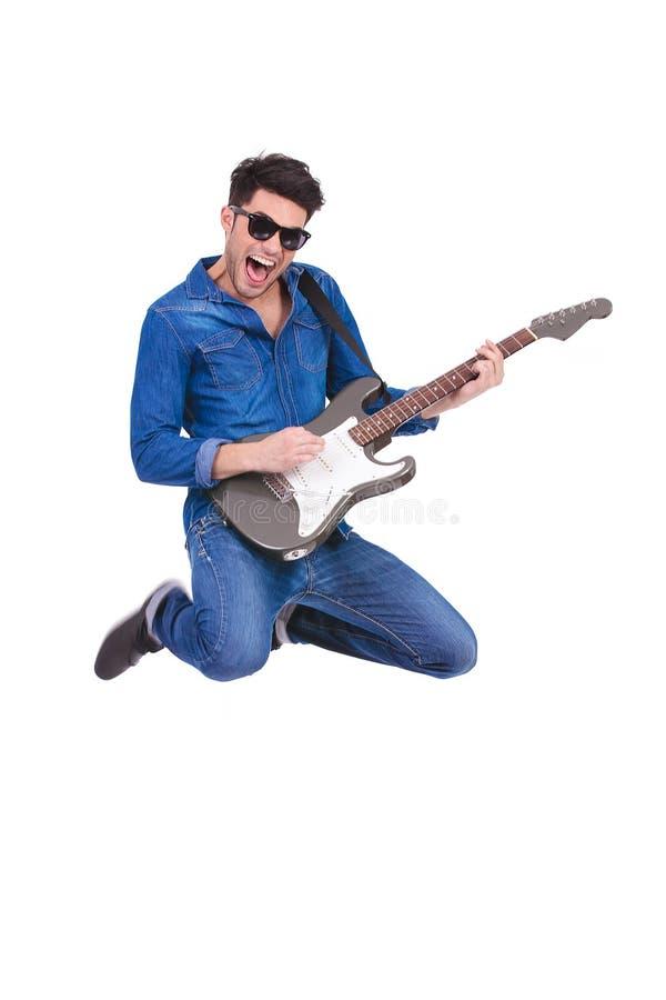 Schreiender Gitarrist springt beim Spielen seiner E-Gitarre lizenzfreies stockfoto