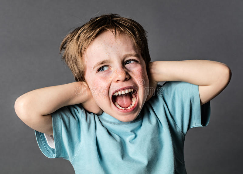 Schreiender Junge, der unter den inländischen Schmerz bedecken seine Ohren leidet stockfoto