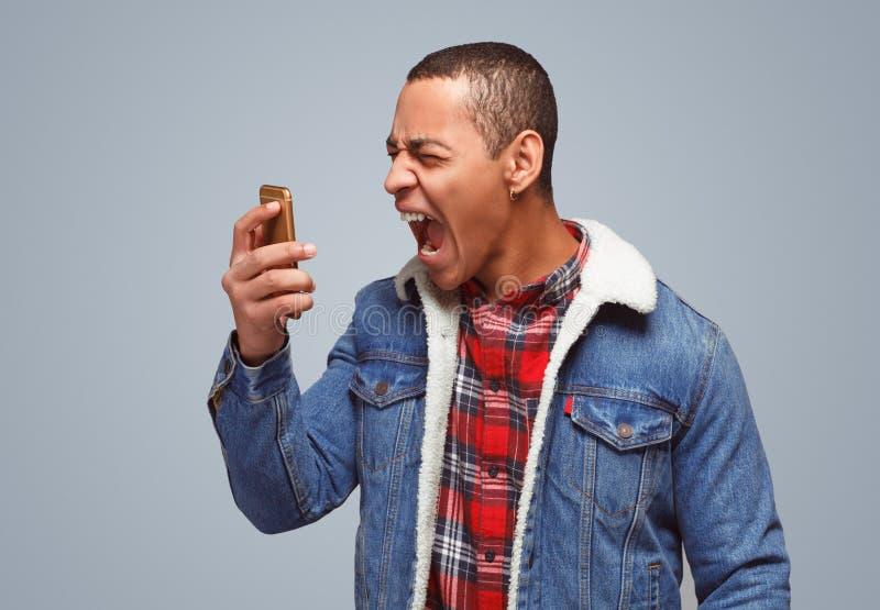 Schreiender Mann mit Telefon in der Raserei stockbild