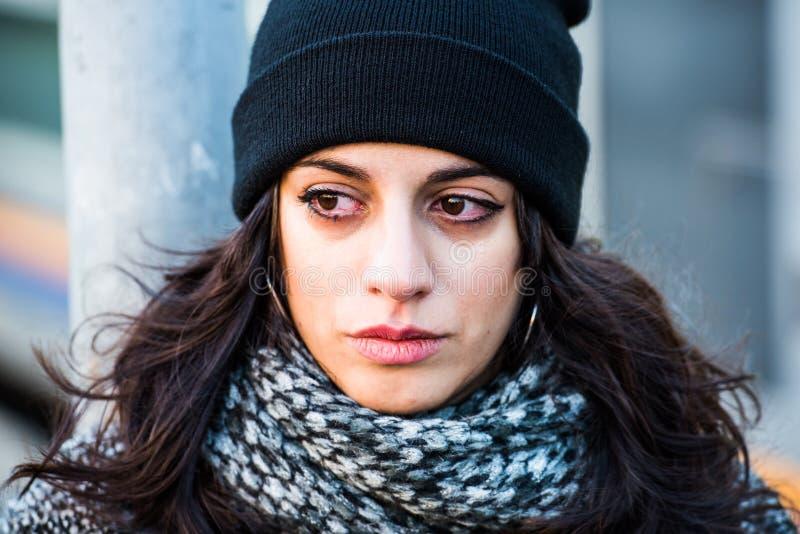 Schreiender trauriger schöner Jugendlicher mit schwarzem Hut und grauem Mantel - naher hoher Makroschuß lizenzfreies stockbild