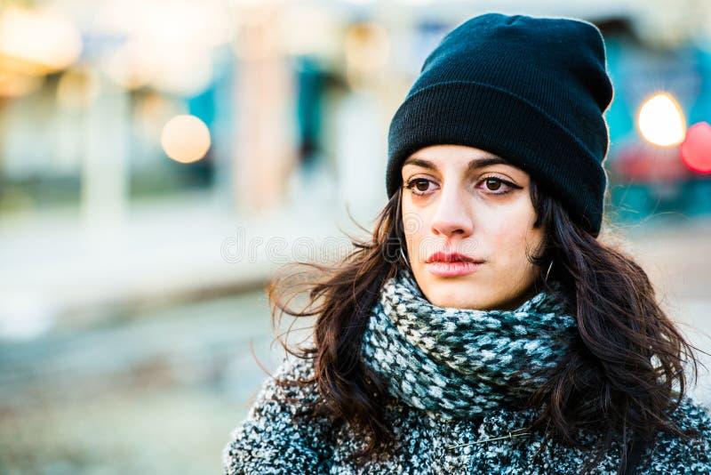 Schreiender trauriger schöner Jugendlicher mit schwarzem Hut und grauem Mantel - naher hoher Schuss stockfotografie