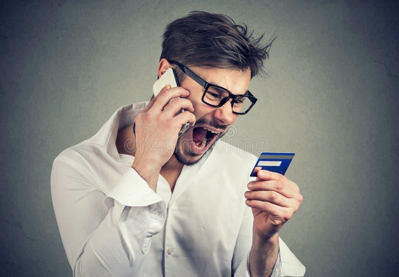 Schreiender verärgerter Mann, der Probleme mit Kreditkarte löst stockfoto