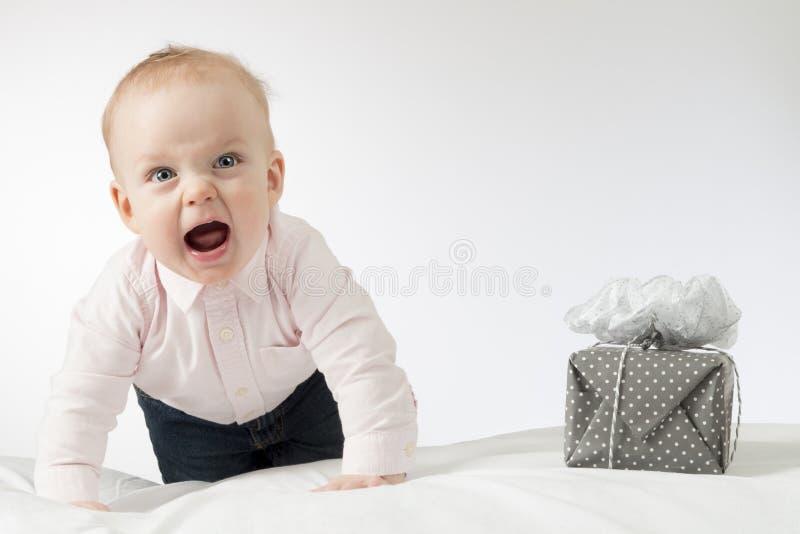 Schreiendes kriechendes Säuglingsbaby, das Kamera betrachtet Kleinkindkind mit einem Geschenk auf der weißen Decke Horizontaler s stockbild
