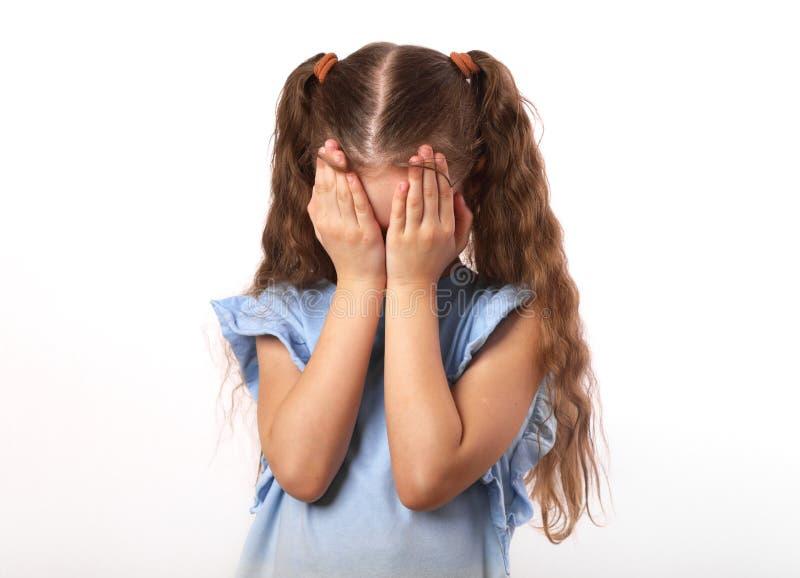 Schreiendes unglückliches Kindermädchen schloss die Hände das Gesicht auf weißem backg lizenzfreie stockbilder