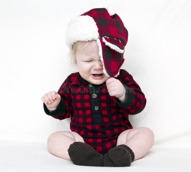 Schreiendes Weihnachtsschätzchen, das versucht, Hut hinabzuziehen lizenzfreie stockfotos