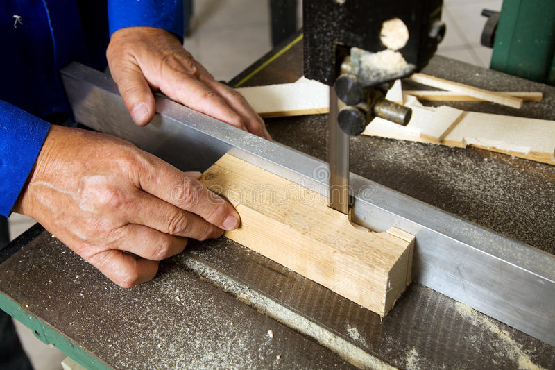 Schreiner on a band saw. An elderly carpenter on a band saw in a carpenter royalty free stock photos