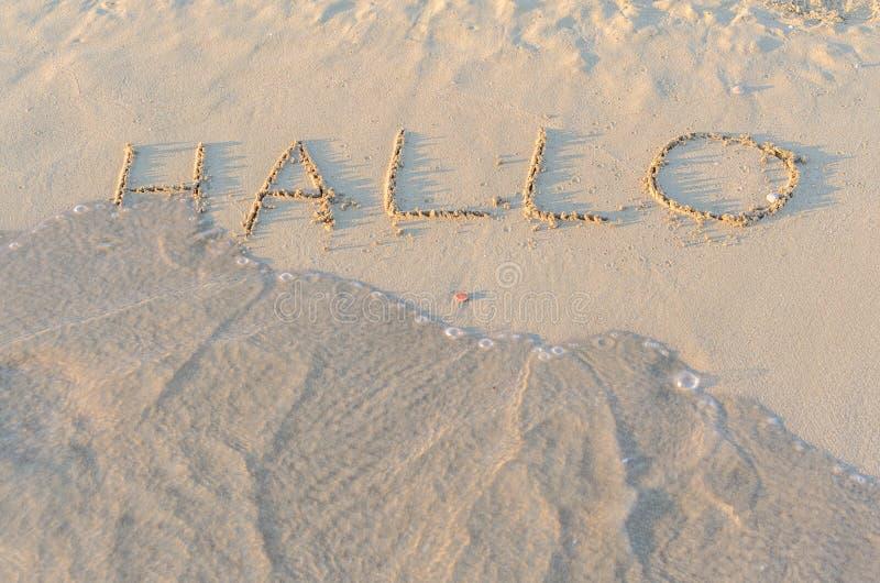 Schriftliche Wörter hallo auf Sand des Strandes lizenzfreie stockbilder