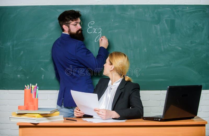 Schrijf uw taak neer Controlethuiswerk Leraren die in het klaslokaal van de parenschool werken Schoolopvoeder en leraarsstagiair stock afbeeldingen