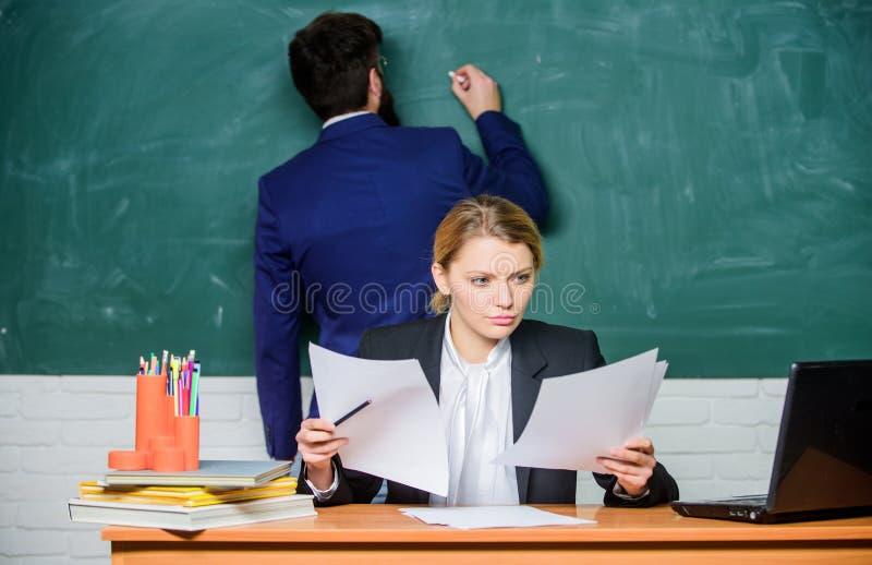 Schrijf uw taak neer Leraren die in het klaslokaal van de parenschool werken Schoolopvoeder en leraarsstagiair met documenten stock foto's