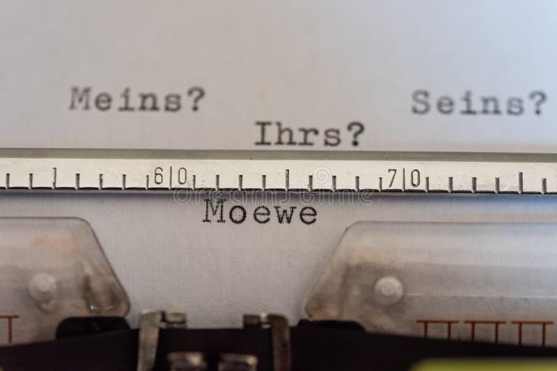 Schrijfmachine met een blad en de woorden Meins? , Seins? , Ihrs? und Moewe-Mijn? , Van hem? , Van u? en Moewe royalty-vrije stock foto