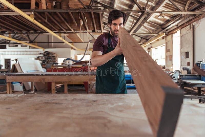 Schrijnwerker die skillfully een houten plank in zijn workshop inspecteren stock fotografie