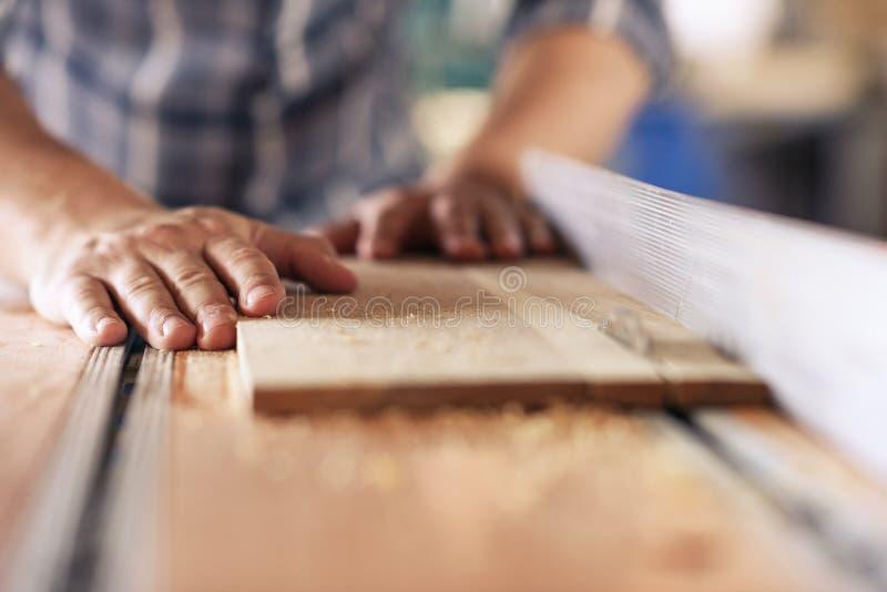 Schrijnwerker zagende planken van hout in zijn timmerwerkworkshop stock foto