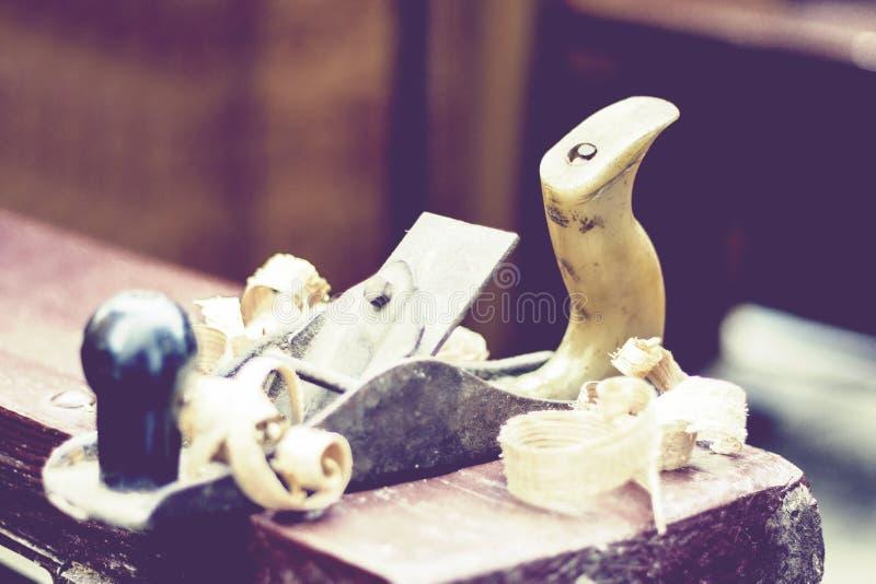 """Schrijnwerkerij†""""oud houten vliegtuig en spaanders in een workshop van de timmerman, retro concept royalty-vrije stock afbeeldingen"""