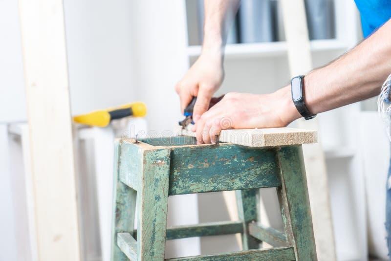 Schrijnwerkerij: de meubilairmeester herstelt de oude dilapidated kruk Uit het scheuren van een oude spijker met tangen royalty-vrije stock foto's