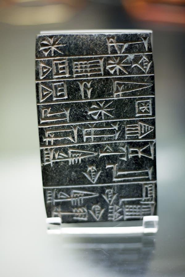 Schrijvend op de steenmuur van de oude Zwarte steatiettablet, poetste de ingesneden wigvormige inschrijving oppervlakten op Heers stock foto