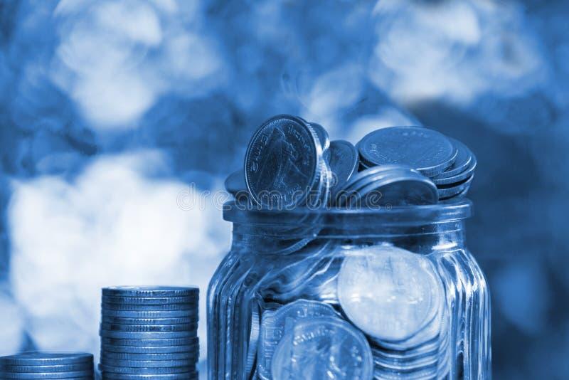 Schritt von Münzenstapeln und von Goldmünzgeld im Glasgefäß auf Vorsprung stockfotografie