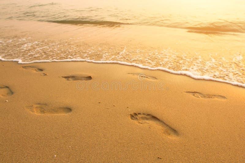 Schritte auf dem Strand durch das Meer stockbilder