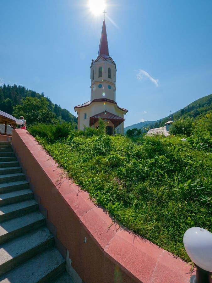 Schritte der Treppe, die zur Kirche mit einem hohen spitzen Dach und zu einem Kreuz auf ihm mit der Sonne auf ihr führt lizenzfreie stockfotografie