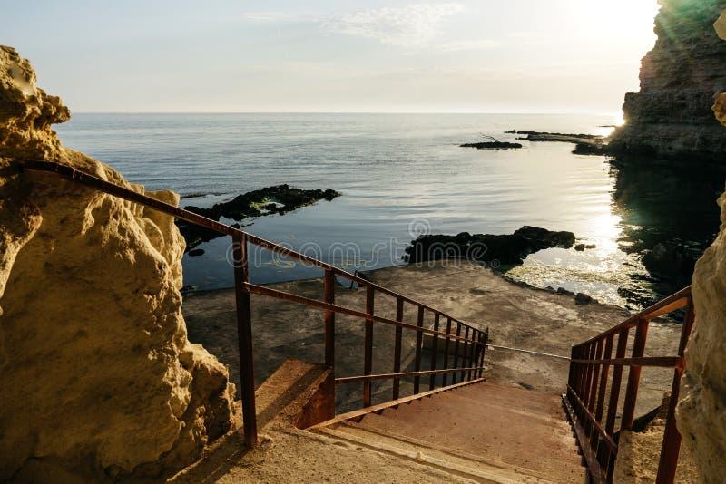 Schritte zum Seesteinstrand Die untergehende Sonne wird im Wasser reflektiert stockfotografie