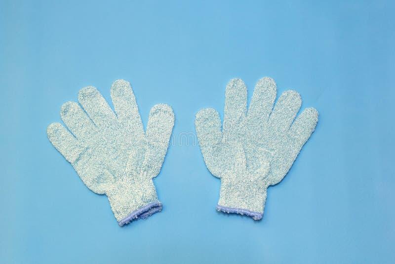Schrobben de blauwe handschoenen van de badmassage voor douche met het exfoliating van hydroschil effect op zachte blauwe achterg stock afbeelding