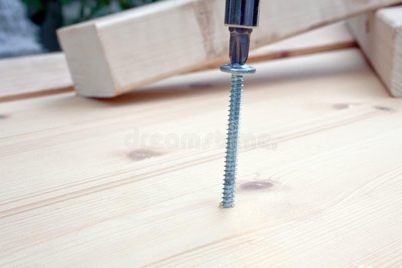 Schroevedraaier, schroef en houten planken stock fotografie