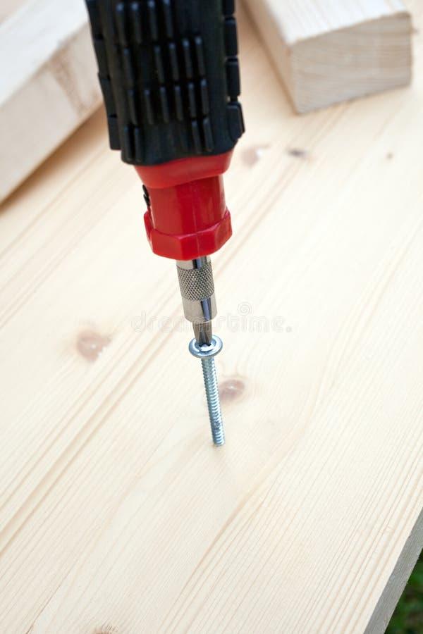 Schroevedraaier, schroef en houten planken. verticaal schot stock foto