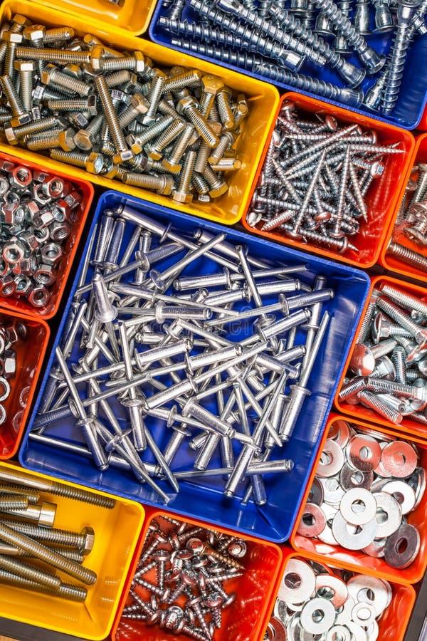 Schroeven in een kleurrijke doos worden gevestigd die stock fotografie