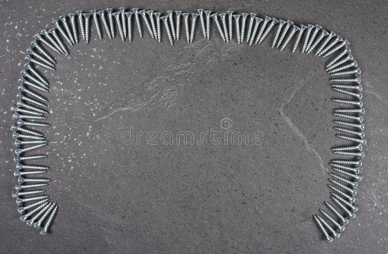 Schroeven op grijze houten achtergrond met exemplaarruimte voor uw eigen tekst voor een uitnodiging voor een workshop stock afbeelding