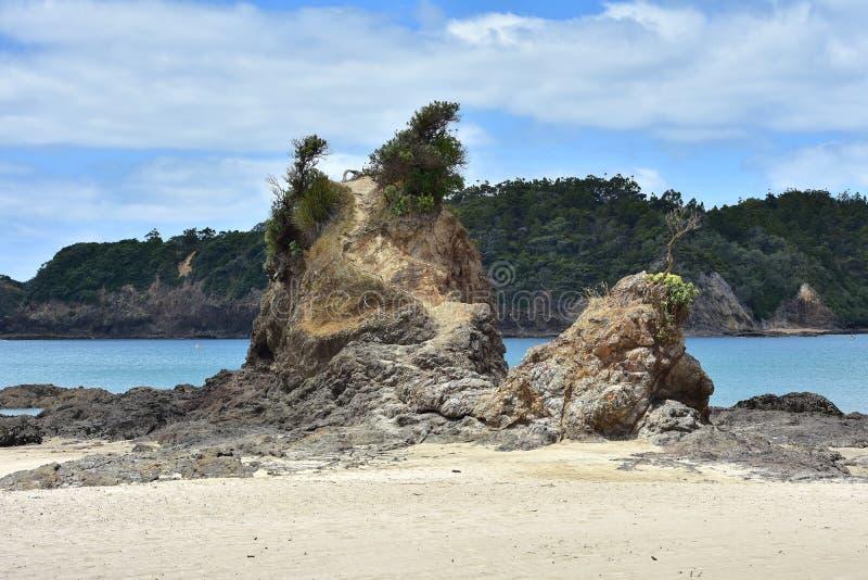Schroffe Felsformation auf sandigem Strand stockbild