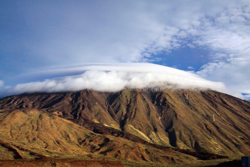 Schroffer Vulkankegel Pico del Teide mit knuddeliger weicher weißer tiefer hängender Kumuluswolkenkappe auf Kanarischer Insel Ten lizenzfreie stockfotografie
