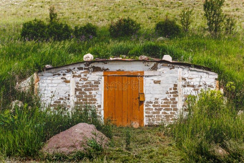 Schron z drewnianym drzwi w wzgórzu z zieloną trawą w wiejskiej średniorolnej ` s miejscowości obraz royalty free