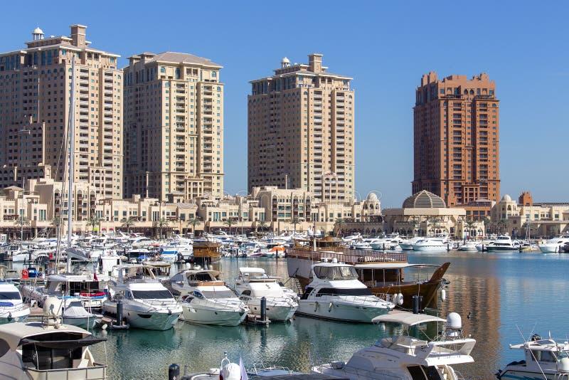 Schronienie widok w Perełkowej dzielnicie Doha, Katar, z jachtami, łodziami i budynkami w budowie w tle, zdjęcie royalty free