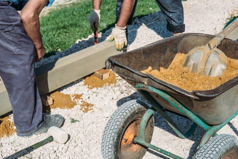 Schubkarre mit den Sand- und Arbeitskrafthänden auf Baustelle lizenzfreie stockfotografie