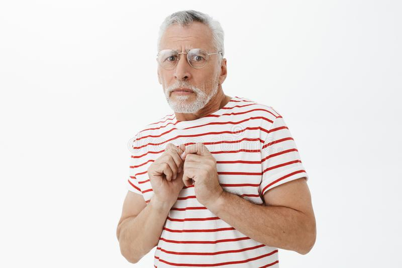 Schuchtere en onzekere hogere mens in gestreepte t-shirt met grijze haar en baard dringende handen aan lichaam van vrees en bezor royalty-vrije stock afbeelding