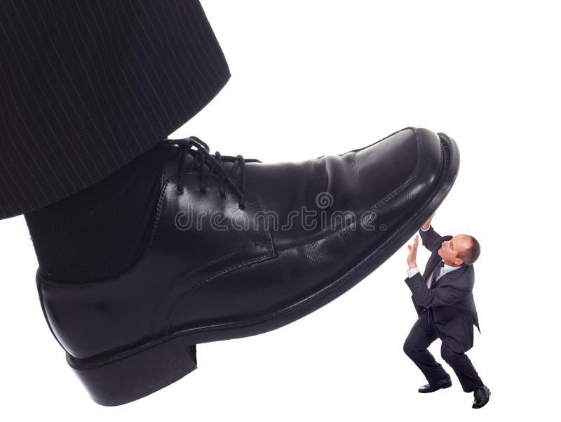 Schuh, der einen Geschäftsmann zerquetscht stockbilder