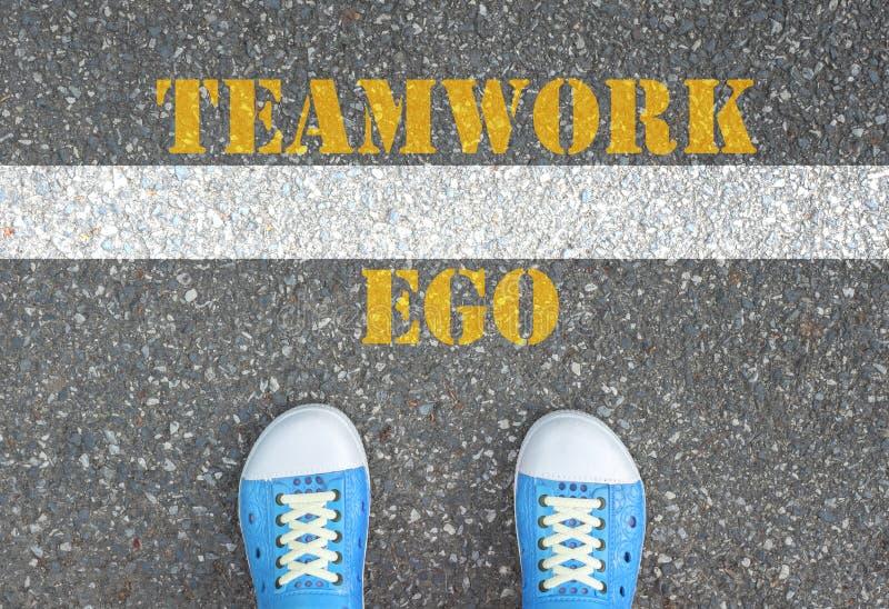 Schuhe, die an der Linie zwischen Ego und Teamwork stehen stockfoto