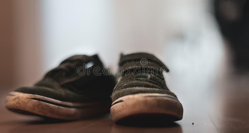 Schuhe eines abgenutzte grüne Flausches der kleinen Jungen auf einem Bretterboden stockbilder