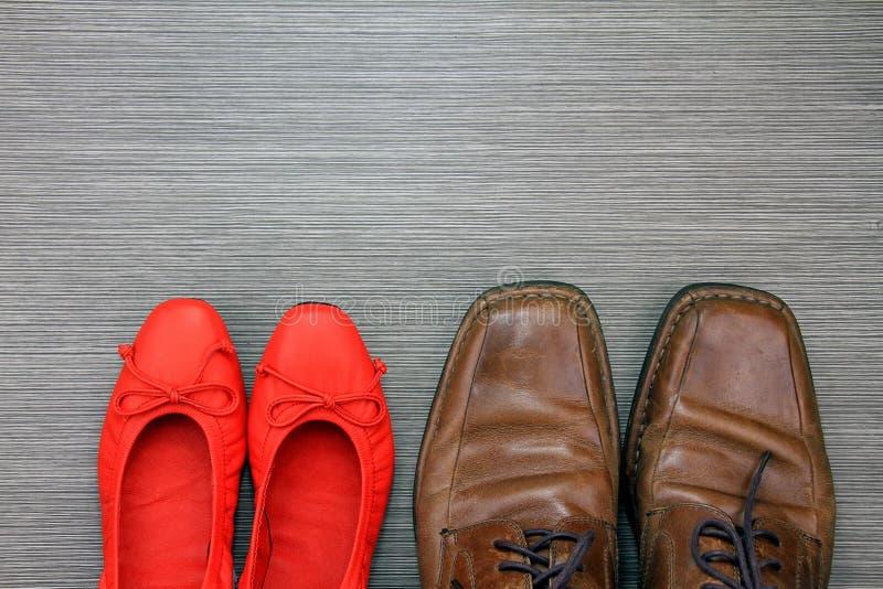 Schuhe eines Mannes und der Frau auf dem Boden, Mode-Accessoires stockfotos