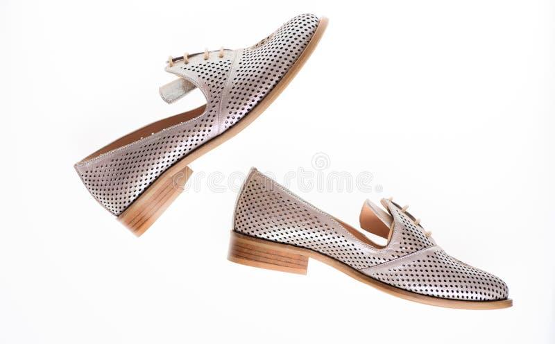 Schuhe hergestellt aus silbernem Leder heraus auf dem weißen Hintergrund, lokalisiert Paare der modernen bequemen Müßiggängerschu lizenzfreies stockbild