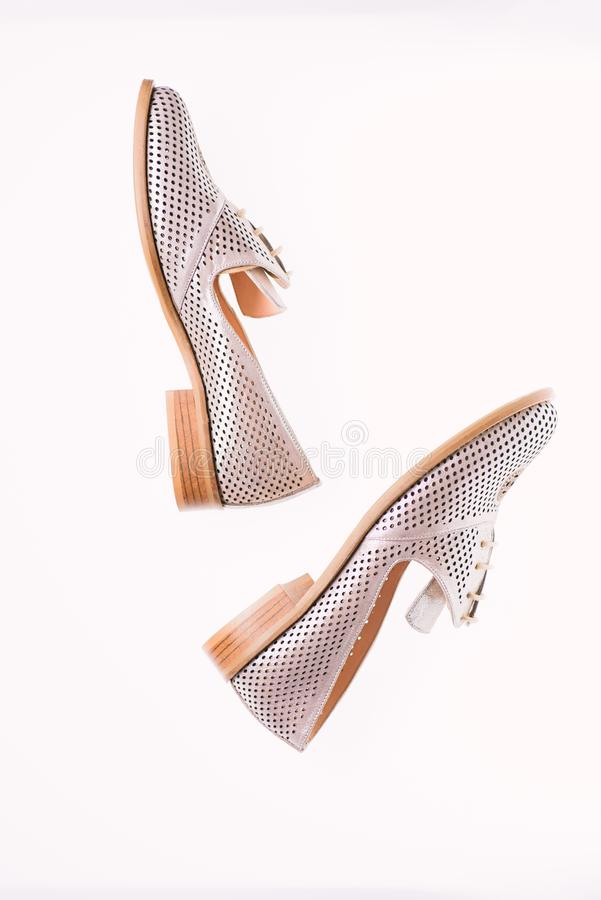 Schuhe hergestellt aus silbernem Leder heraus auf dem weißen Hintergrund, lokalisiert Weibliches Schuhekonzept Schuhe für Frauen  stockbild