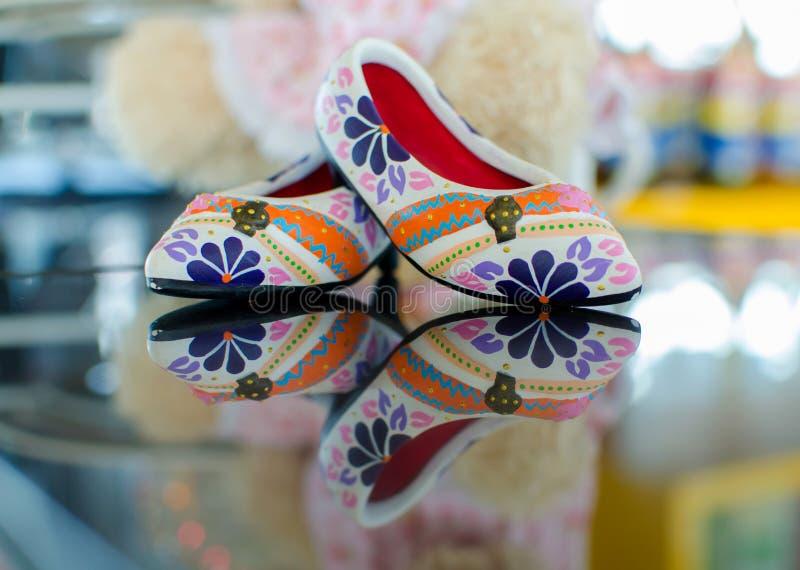 Schuhe mit Blumenverzierung auf Glas und Reflexion lizenzfreie stockbilder