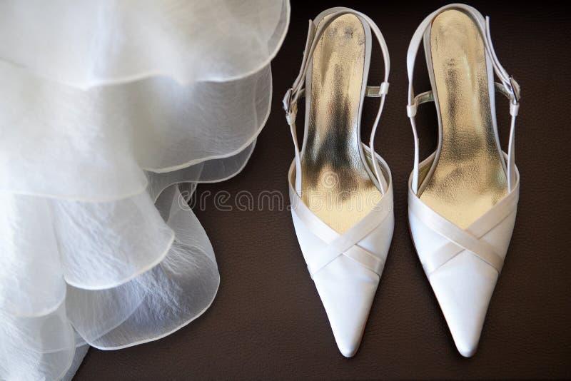 Schuhe mit Hochzeitskleid stockfotos