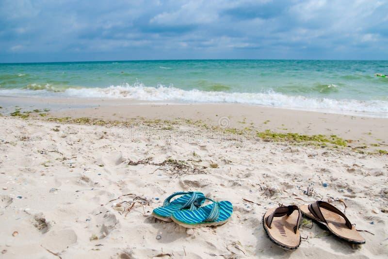 Schuhe nähern sich Meer lizenzfreie stockbilder