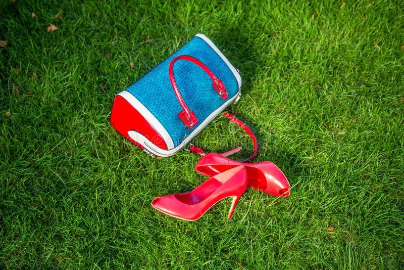 Schuhe und die Handtasche der Frauen legen auf das Gras, die Schuhe der Frauen lizenzfreie stockfotos