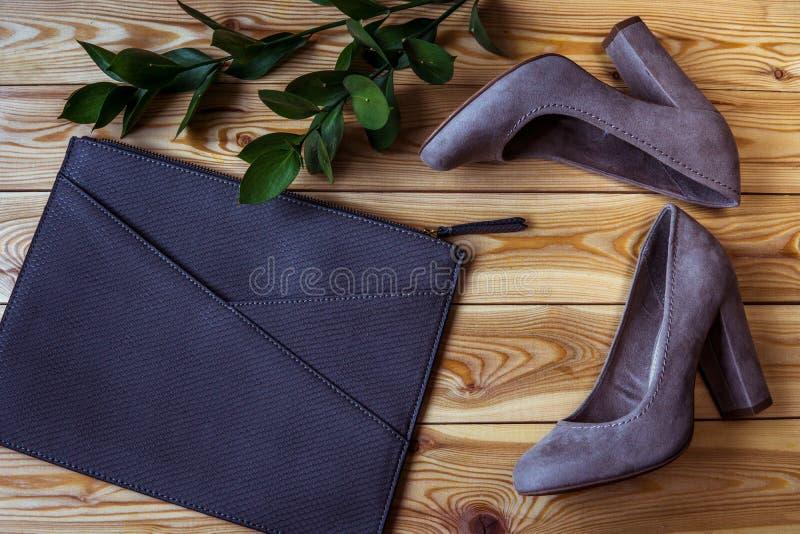 Schuhe und Kupplung auf einer Draufsicht des hölzernen Hintergrundes Art und Weiseset stockfoto