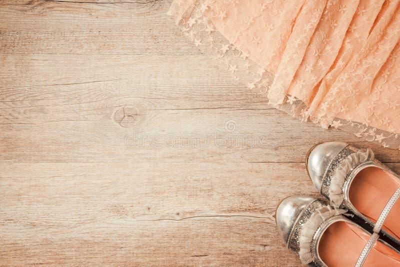 Schuhe und Partykleid des jungen Mädchens auf hölzernem Hintergrund Retro- Filtereffekt stockfotografie