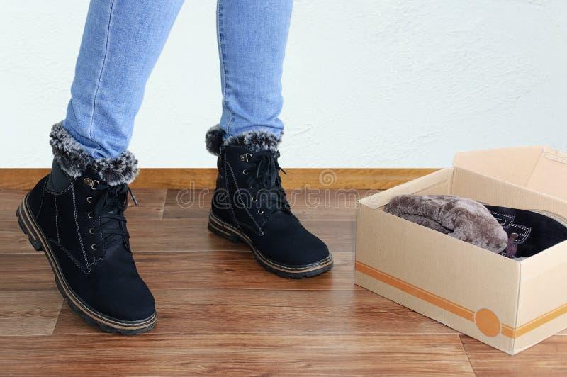 Schuhversuche Legs eines Mädchens in blauer Jeans und schwarzen Winterstiefeln stockbilder